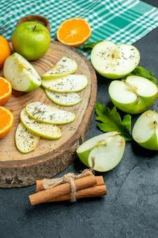 Vista inferior, corte maçãs e tangerinas na tábua de madeira canela na toalha de mesa verde na mesa escura