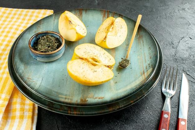 Vista inferior, corte maçãs secas com hortelã em uma tigela, colher de pau na faca do prato e um garfo amarelo toalha de cozinha em solo escuro