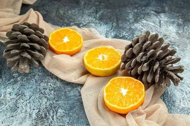 Vista inferior, corte pinhas de laranjas em xale bege em superfície escura