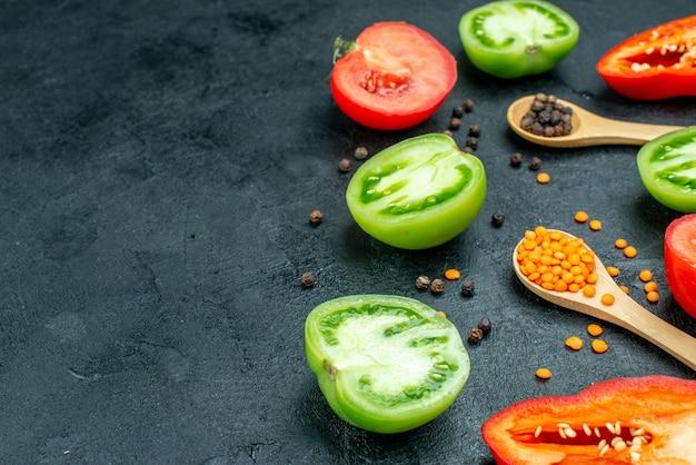 Vista inferior corte vegetais verdes e vermelhos tomates pimentões vermelhos aconchegantes lentilhas vermelhas pimenta preta em colheres de madeira na mesa com espaço livre
