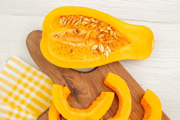 Vista inferior da abóbora picada na tábua de cortar abóbora cortada ao meio toalha de cozinha quadriculada branca amarela na mesa cinza