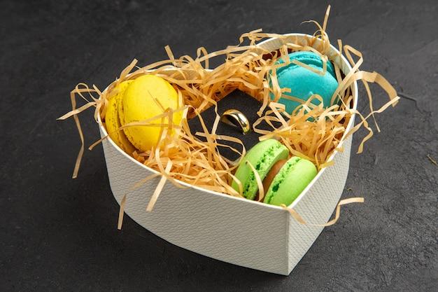 Vista inferior da caixa em forma de coração com anel de noivado de macarons na mesa