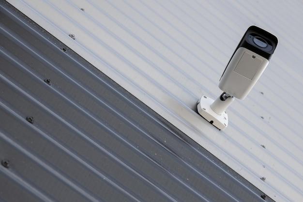 Vista inferior da câmera de monitoramento de vídeo preto e branco de alta tecnologia na parede ondulada em preto e branco