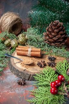 Vista inferior da canela em pó na colher na tábua de madeira canela em pau de pinha no escuro