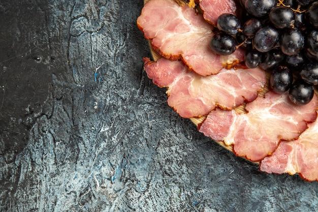 Vista inferior da carne fatiando uvas e romã em uma mesa oval em um espaço livre de fundo escuro