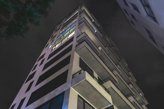 Vista inferior da casa residencial alta moderna à noite. exteriores de apartamentos de luxo à noite ensolarada. empréstimo de apartamento.