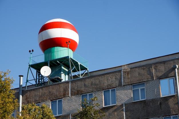 Vista inferior da esfera vermelho-branca na construção do serviço meteorológico contra o céu azul