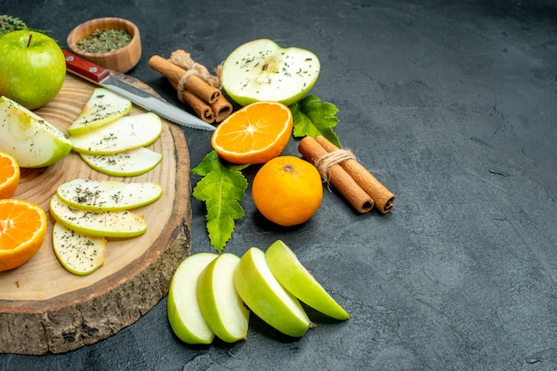 Vista inferior da faca de fatias de maçã e tangerina na tábua de madeira em bastões de canela amarrados com pó de menta seca por corda na mesa preta espaço livre