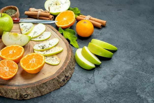Vista inferior da faca de fatias de maçã e tangerinas na placa de madeira em bastões de canela amarrados com pó de menta seca em uma tigela na mesa preta