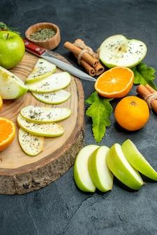 Vista inferior da faca de fatias de maçã e tangerinas na placa de madeira em bastões de canela amarrados com pó de menta seca por corda em fundo escuro