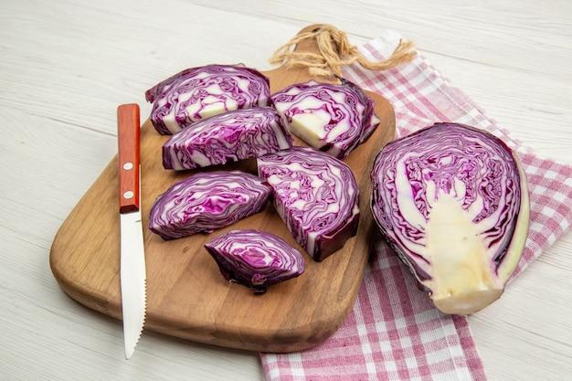 Vista inferior da faca de repolho roxo picado na placa de madeira na toalha de cozinha quadriculada rosa branca na mesa cinza