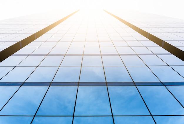 Vista inferior da janela do edifício de escritórios perto com o nascer do sol, reflexão e perspectiva