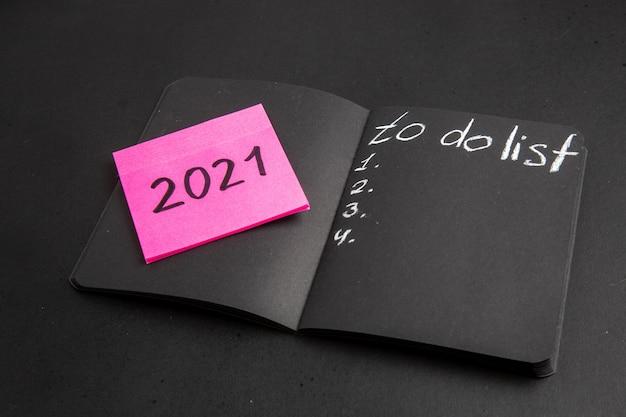 Vista inferior da lista de tarefas escrita em um bloco de notas preto escrito em uma nota adesiva rosa em fundo preto