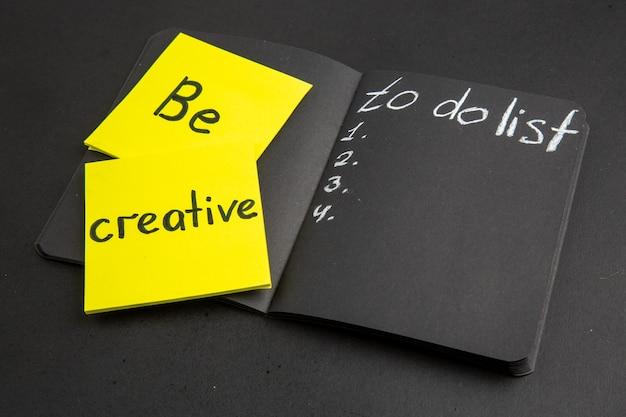 Vista inferior da lista de tarefas escrita em um bloco de notas preto. seja criativo escrito em uma nota adesiva amarela sobre fundo preto