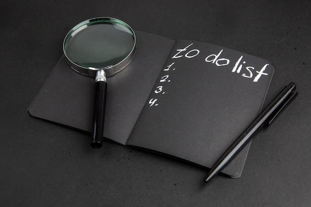 Vista inferior da lista de tarefas escrita no bloco de notas preto lupa pen na mesa preta