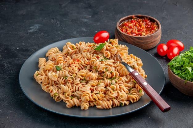 Vista inferior da massa rotini com garfo de tomate cereja no prato salsa e molho de tomate em tigelas tomate cereja na mesa escura