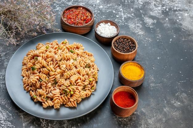 Vista inferior da massa rotini em prato redondo, molho de tomate, especiarias diferentes em pequenas tigelas na mesa escura