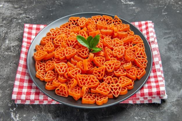 Vista inferior da massa vermelha italiana em forma de coração em prato oval preto em toalha de cozinha em superfície escura