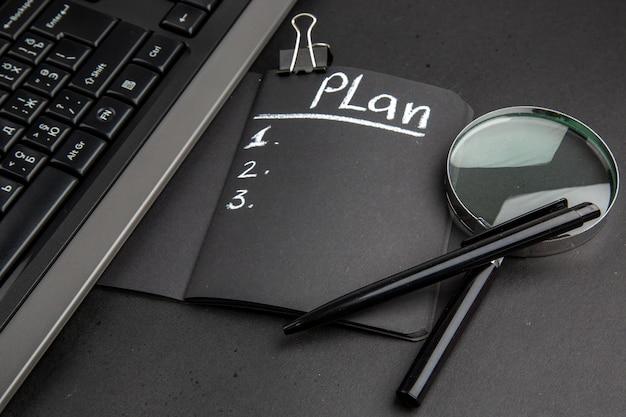 Vista inferior da planta escrita no bloco de notas preto lupa, caneta e clipe de fichário em fundo preto