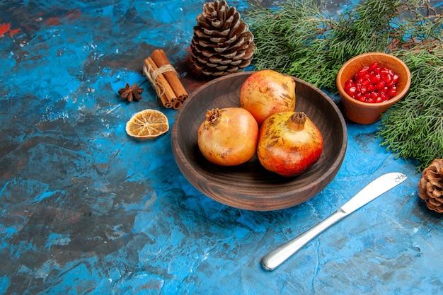 Vista inferior da romã na placa de madeira sementes da romã em uma tigela de madeira galho de árvore de pinho e canela de canela em fundo azul.