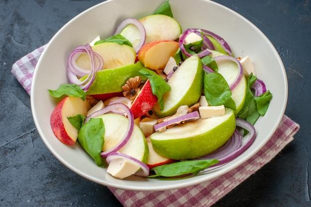 Vista inferior da salada de maçã em uma tigela, guardanapo xadrez branco rosa na mesa escura