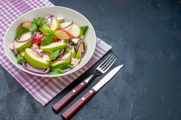 Vista inferior da salada de maçã em uma tigela quadriculada roxa e branca com faca e garfo em mesa escura.