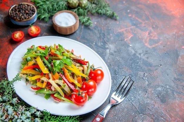 Vista inferior da salada de vegetais em prato oval garfo de tomate cereja em superfície vermelha escura