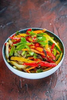 Vista inferior da salada de vegetais em uma tigela na mesa vermelha escura