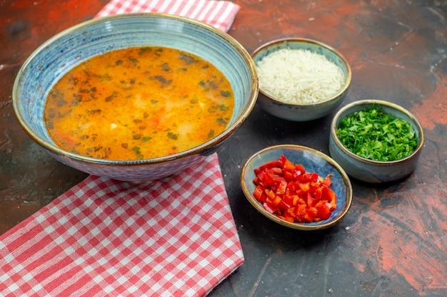 Vista inferior da sopa de arroz em uma tigela em uma toalha de mesa quadriculada branca e vermelha, outros alimentos em tigelas na mesa