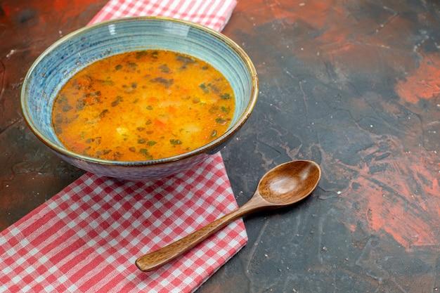 Vista inferior da sopa de arroz em uma tigela no pano de cozinha quadriculado branco vermelho colher de pau no espaço livre da mesa