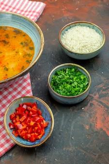 Vista inferior da sopa de arroz em uma tigela sobre uma toalha de mesa quadriculada branca e vermelha alguns outros alimentos em tigelas na mesa