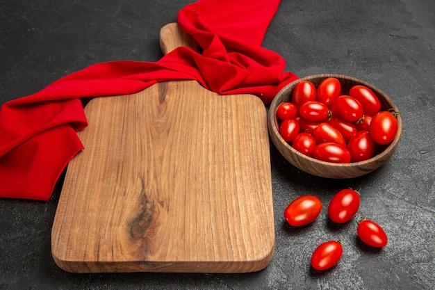 Vista inferior da tigela com tomate cereja, toalha vermelha, tábua de cortar e tomate cereja em fundo escuro