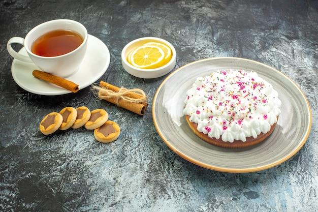 Vista inferior da xícara de chá, fatias de limão em um pequeno pires, bolo em prato redondo, biscoitos em paus de canela na mesa escura