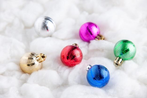 Vista inferior das bolas coloridas da árvore de natal na superfície branca