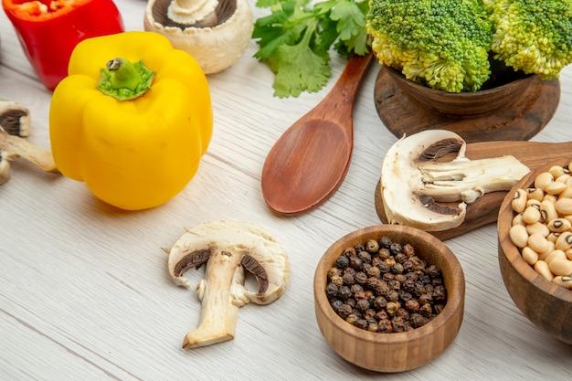 Vista inferior das cenouras na tábua de cortar cogumelos diferentes especiarias em tigelas, pimentões, colheres de madeira na mesa