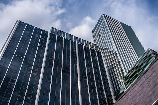 Vista inferior das fachadas dos arranha-céus de vidro modernos do escritório contra o céu azul. baixo ângulo de tiro.