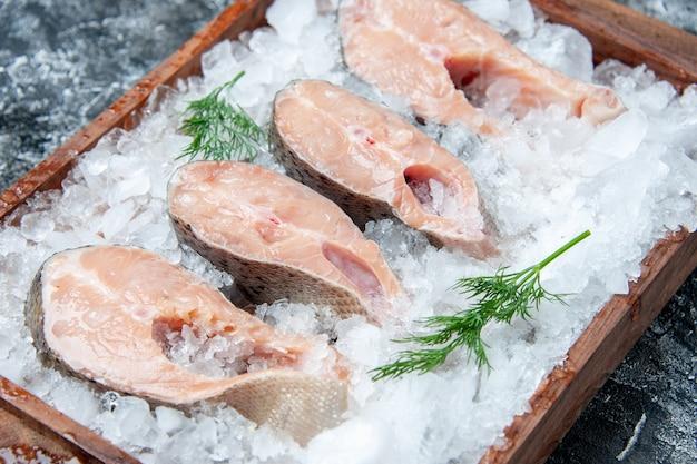 Vista inferior das fatias de peixe cru com gelo na placa de madeira