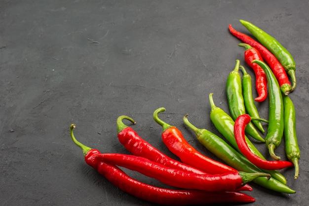 Vista inferior das pimentas vermelhas e verdes no lado direito da mesa preta