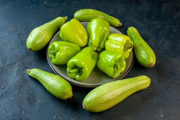 Vista inferior de abobrinhas de diferentes tamanhos ao redor de pimentões verdes em um prato redondo cinza na superfície escura