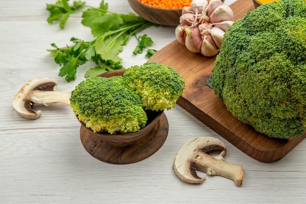 Vista inferior de alho brócolis fresco na tábua de cortar cogumelos salsa na mesa cinza