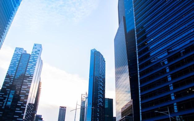 Vista inferior de arranha-céus / prédios de escritórios modernos no distrito financeiro das cidades de singapura contra o céu azul. economia, finanças, conceito de atividade de negócios. copie o espaço para o conteúdo.