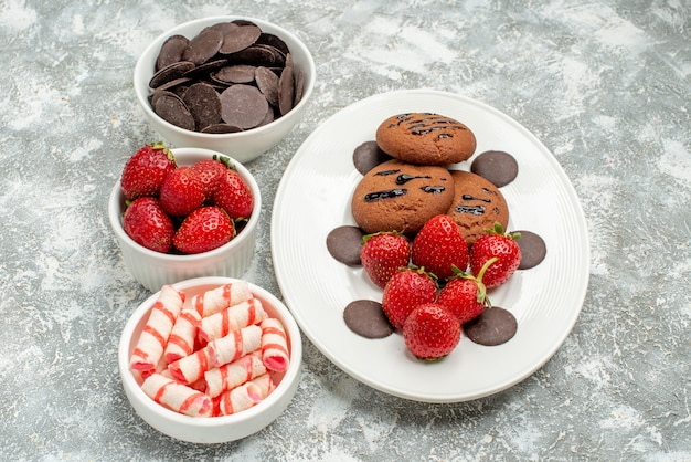 Vista inferior de biscoitos de chocolate, morangos e chocolates redondos no prato oval branco e tigelas com doces e morangos chocolates no centro da mesa cinza-esbranquiçada