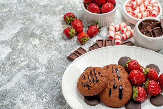 Vista inferior de biscoitos, morangos e chocolates redondos no prato branco e tigelas de doces e morangos chocolates na mesa cinza-esbranquiçada