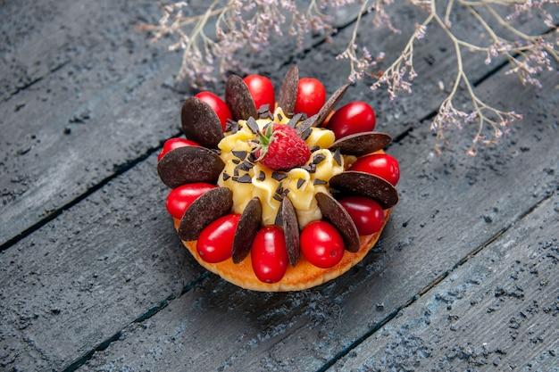 Vista inferior de bolo com fruta cornel, framboesa e chocolate no fundo escuro de madeira