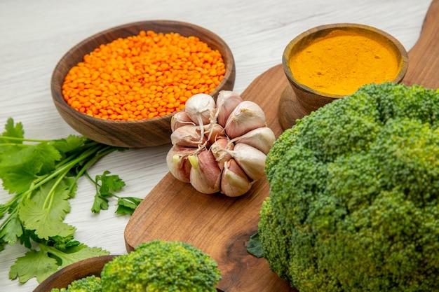 Vista inferior de close-up brócolis alho açafrão na tábua de cortar salsa tigela de lentilha na mesa cinza
