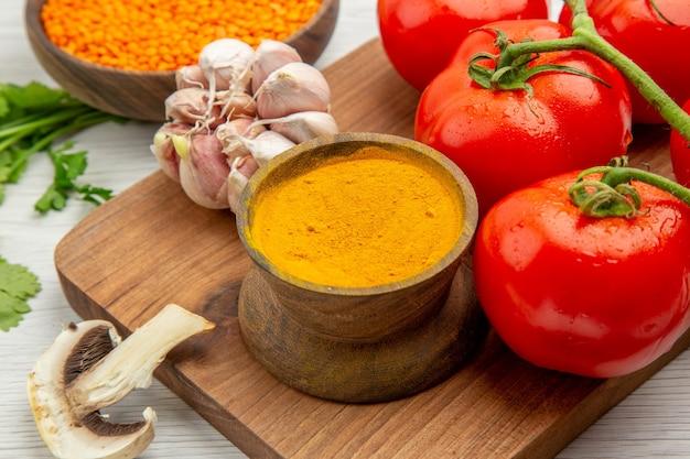 Vista inferior de close-up ramo de tomate fresco alho açafrão na tábua de picar cogumelos na mesa cinza