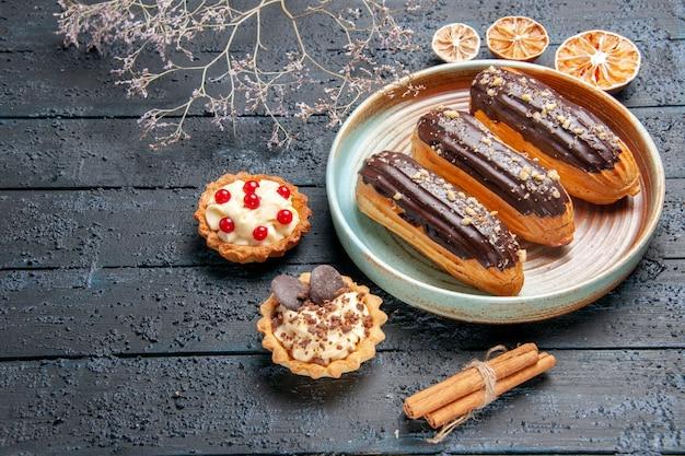 Vista inferior de éclairs de chocolate em prato oval tortas de galho de flores secas e laranjas secas na mesa de madeira escura com espaço de cópia