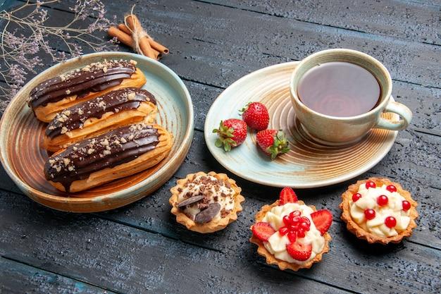 Vista inferior de éclairs de chocolate em prato oval, uma xícara de chá e morangos em tortas de pires e canela na mesa de madeira escura