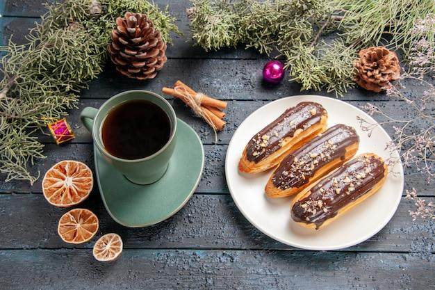 Vista inferior de éclairs de chocolate em uma placa oval branca, galhos e cones de pinheiro, brinquedos de natal e uma xícara de chá na mesa de madeira escura