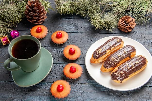 Vista inferior de éclairs de chocolate em uma placa oval branca ramos de pinheiro-alvarinho brinquedos de natal, biscoitos e uma xícara de chá no chão de madeira escura
